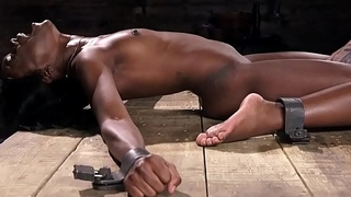 Shackled ebony in device fucks machine